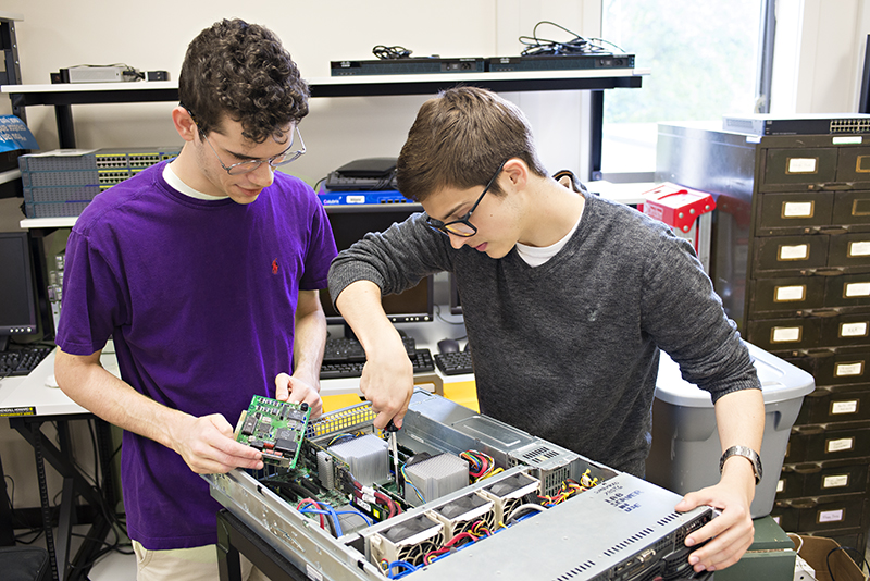 Photo of two students working on a computer tower