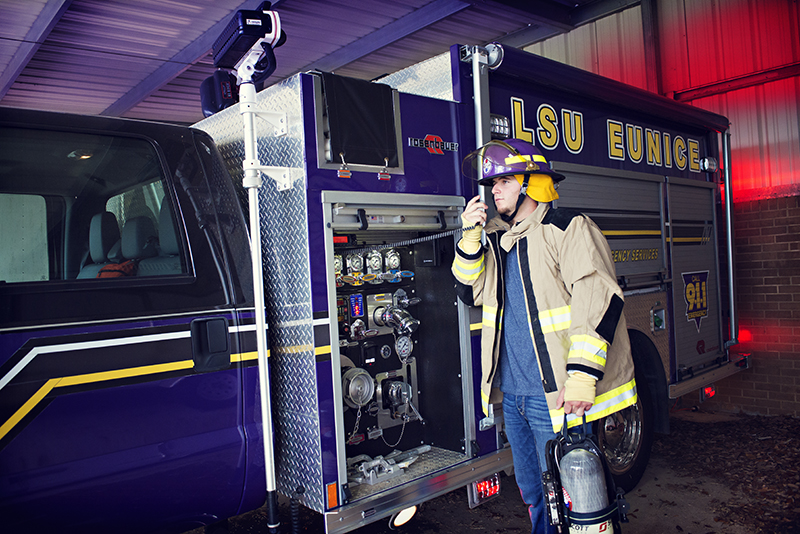 Photo of student on radio next to LSUE fire truck