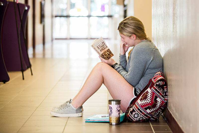Photo of student in hall way reading book