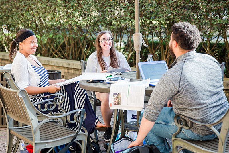 Photo of students chatting around patio table