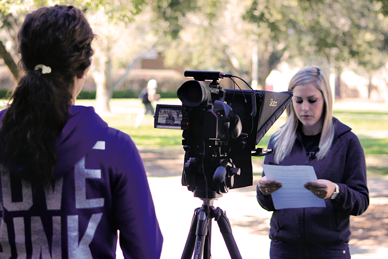Photo of students reading script in front of video camera