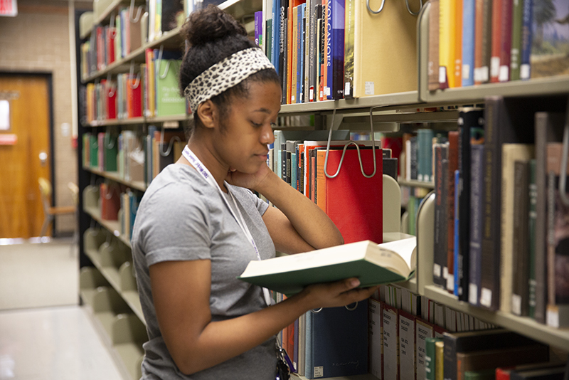 Photo of student in library reading book by shelves
