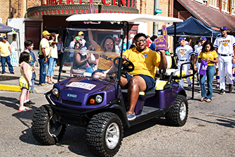LSUE SGA president and Chancellor riding on golf cart in a parade